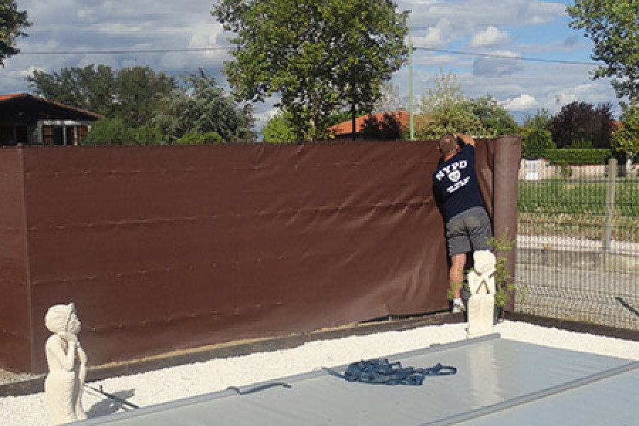 Fixing a privacy screen around a pool Installation in process